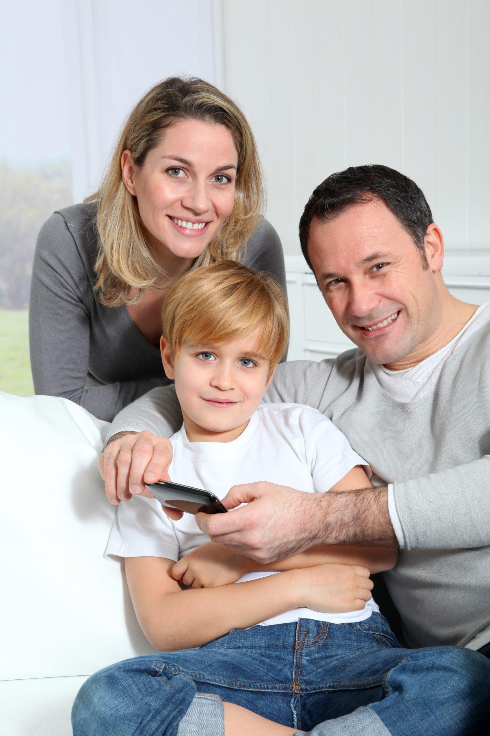 Couple et petit garçon canapé smartphone